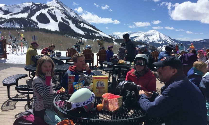 the family having lunch at a picnic table on a mountain at a ski resort