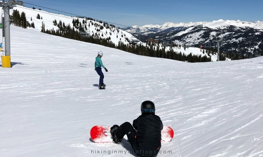 snowboarders at the top of a ski run