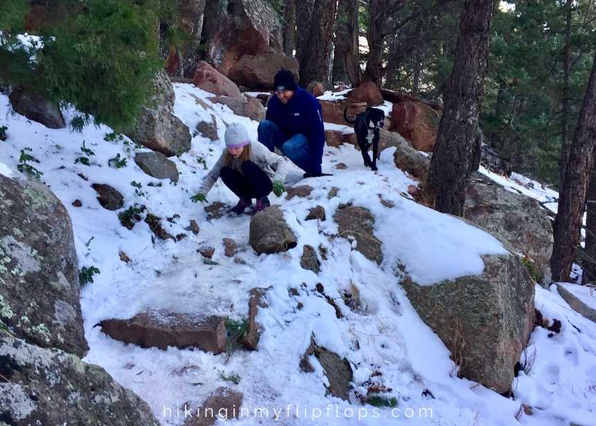 sliding down Mallory Cave trail in the snow in Boulder