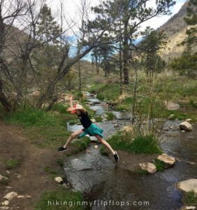 jumping over a creek on a hiking trail