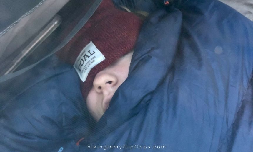 tips for cold weather camping include wearing a beanie when snuggled in your sleeping bag