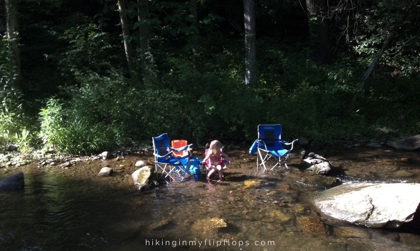a girl sitting in a camp chair in a creek, how to stay cool while camping