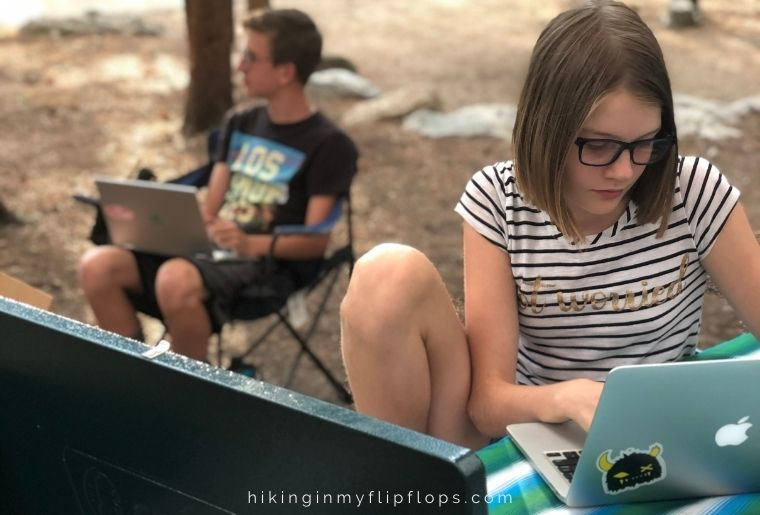 kids doing school work at a campground, one of many things to do when camping