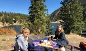 girls having lunch at a picnic table with their favorite road trip foods