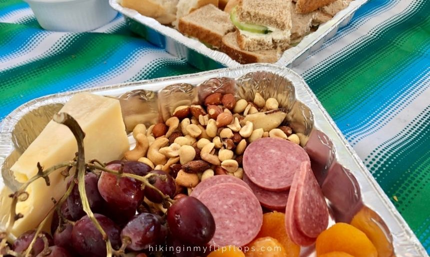 a road trip food list with meats, cheeses, nuts, and fruit can be used for snack boards on the road
