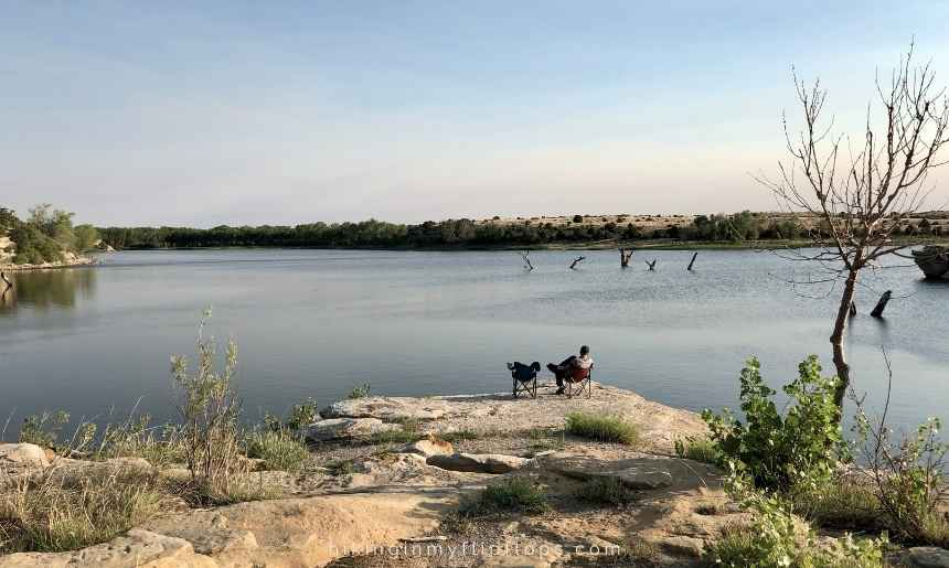 a man sitting in a camp chair taking in the view of a lake in New Mexico appears inspired by one of many great outdoors quotes