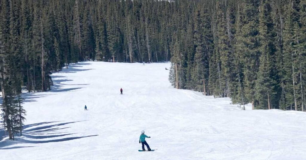 snowboarding on a run at Copper Mountain, one of the best family ski resorts in Colorado